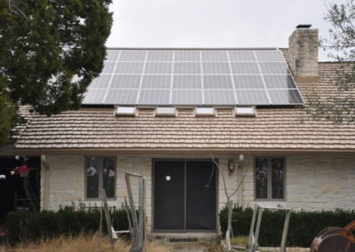 solar panels on stone home with cedar shake roof