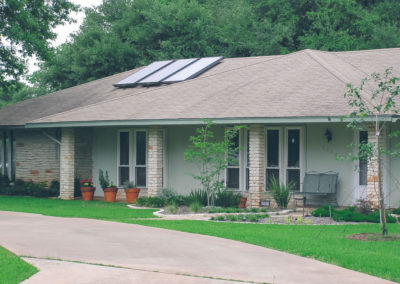 solar panels on grey stucco bungalow
